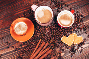 View from above of closely packed mugs full of hot coffee with foam, cinnamon sticks, star anise, coffee beans and wooden board with heart shaped cookies, staying on the wooden table